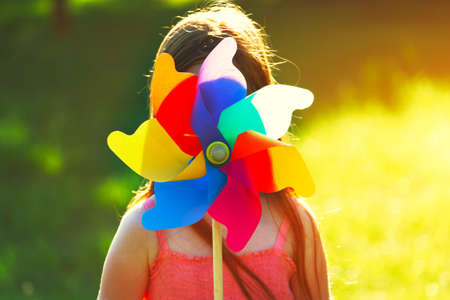 girl with pinwheel toy in park Stock Photo