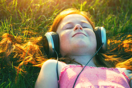 redhead girl with headphones listening to music dreaming Stock Photo