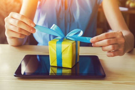 hands with gift box and digital tablet. online shopping concept Archivio Fotografico