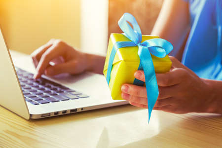 hands with gift box and laptop. online shopping or post shipping concept