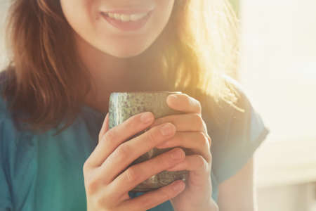 girl drinking cup of coffee or tea in morning sunlight