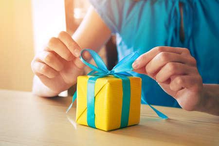 woman making gift box decorating with ribbon Standard-Bild