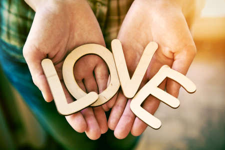 Hands holding wooden letters with word love. Love concept Stock Photo
