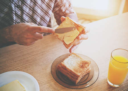 male hands spreading butter on toasted bread while morning breakfast