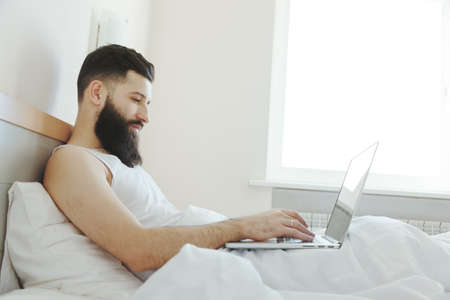 job posting: Bearded man lying in morning bed with laptop working or studying