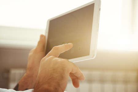 comunicarse: manos de los hombres con la tableta digital mediante la aplicación o la lectura de noticias en la cama por la mañana