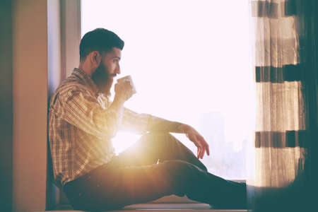 bearded man sitting at window sill and drinking morning coffee in sunrise light Stockfoto