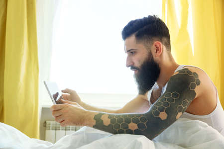 Bearded man lying in morning bed with digital tablet using app or reading news feed Stock Photo