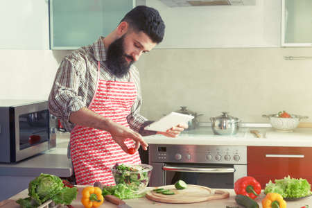 cocina saludable: man cooking at kitchen making healthy vegetable salad and reading receipt on digital tablet Foto de archivo