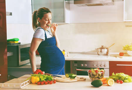 happy pregnant woman on kitchen making healthy salad