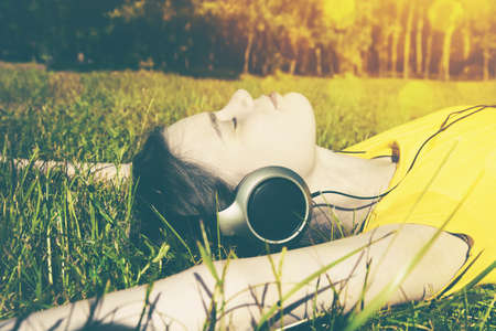 pretty girl lying in summer grass with headphones listening to music and relaxing photo