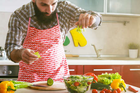 awesome bearded man cooking at kitchen making healthy vegetable salad Stock Photo