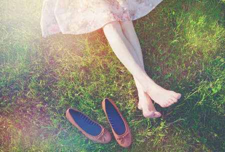 girls legs lying in grass barefoot without shoes Stockfoto