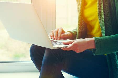 Meisjes handen werken met laptop in de buurt van raam thuis Stockfoto - 80703223