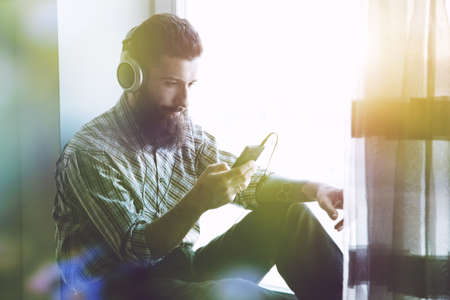 bearded man in headphones listening to music with smartphone app Stock Photo