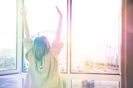 drowsy: Woman near window raising hands facing the sunrise at morning