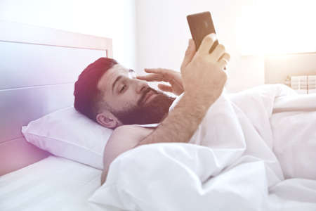 Sleepy man lying in morning bed with phone using app or reading news feed