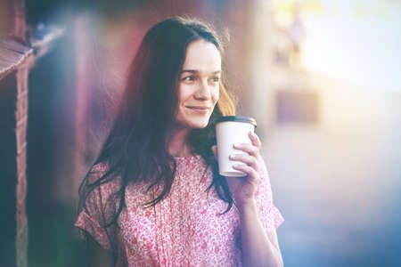 smiling pretty girl walking in street with morning coffee photo
