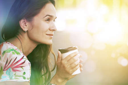 pretty girl sitting in street with morning coffee photo