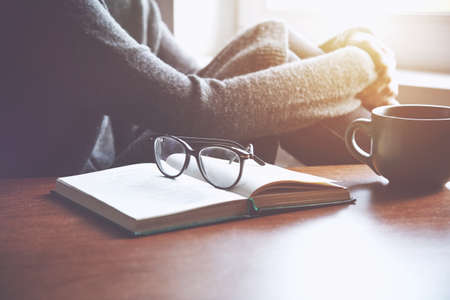 woman resting after reading near book with glasses and cup of tea or coffee