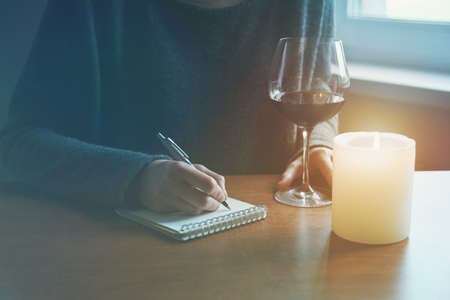 female hands with pen and glass of wine writing on notebook in candle light Reklamní fotografie
