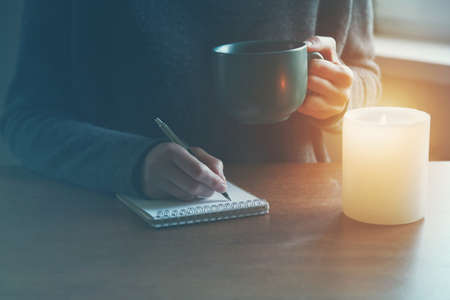 female hands with pen and cup of tea or coffee writing on notebook in candle light Reklamní fotografie