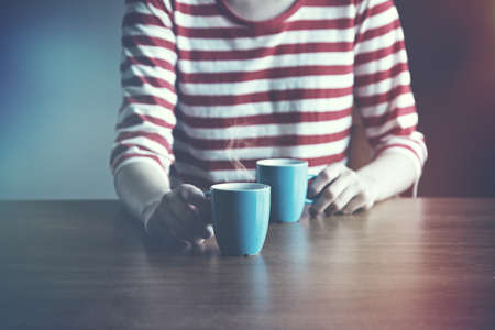 treating: girl with two cups of coffee or tea in morning light offering one for us Stock Photo