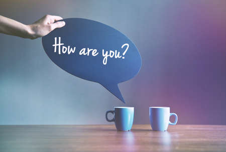 two cups of coffee with bubble plate as dialog with greeting text How are you