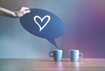 two cups of coffee with bubble plate as dialog with shape of heart as love symbol Stock Photo