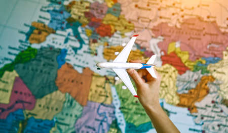 hand with toy model of airplane on world map background