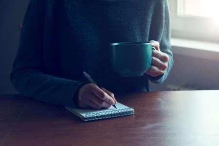 여성의 손에 펜과 차 또는 커피의 컵 노트북에 쓰기