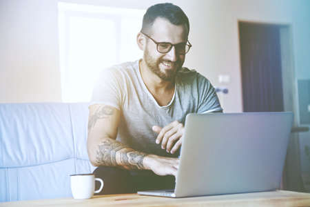 smiling man with laptop typing at coffee table