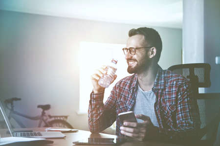 smiling man with smart phone working and drinking water
