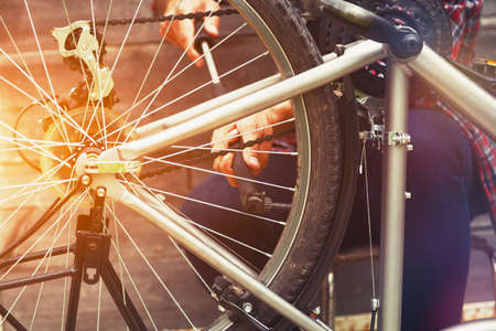man repairing bike pumping wheel