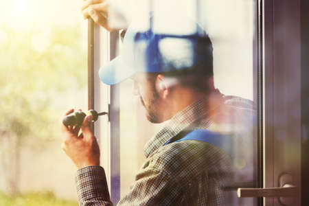 service man installing window with screwdriver Stockfoto