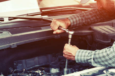 Auto mechanic working with wrench in engine. Car repair service