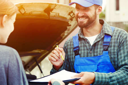 Auto mechanic and car owner signing contract. Car repair service Stock Photo
