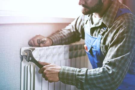 uomo di servizio con chiave vicino radiatore