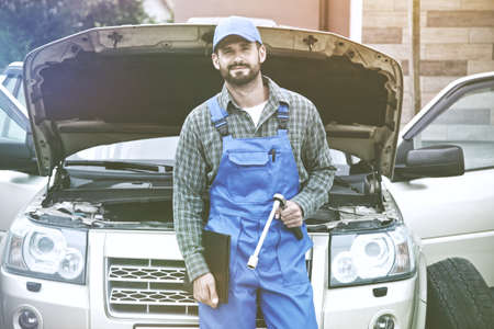 Portrait of auto mechanic working with wrench in engine. Car repair service