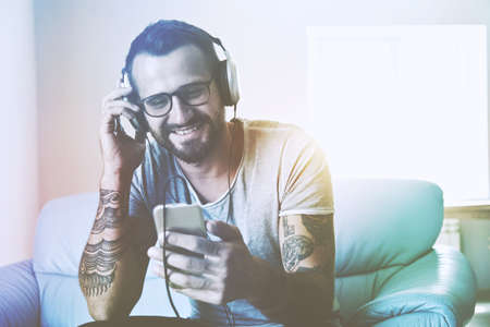 smiling man listening to music with headphones and smart phone Stock Photo