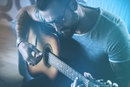 handsome man playing acoustic guitar