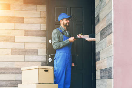 Smiling delivery man with cardboard box giving clipboard to put signature. Stock Photo