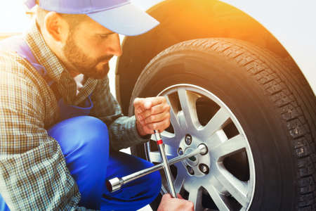mechanic changing car tire with wheel wrench