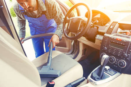 service man with vacuum cleaner cleaning car seat Stock Photo