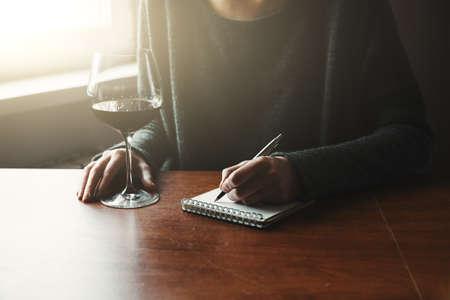 여성의 손에 펜과 노트북에 쓰는 와인 잔 스톡 콘텐츠