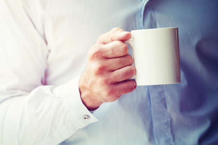 businessman hand holding coffee or tea mug. Blank space for logo or text