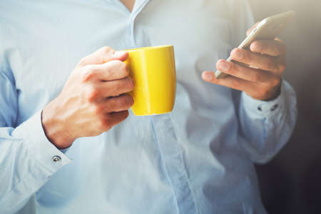 businessman hand holding morning coffee and reading smartphone