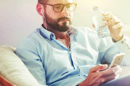 man with smart phone working and drinking water Stock Photo