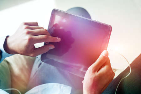 male hands holding digital tablet touching with finger Stock Photo