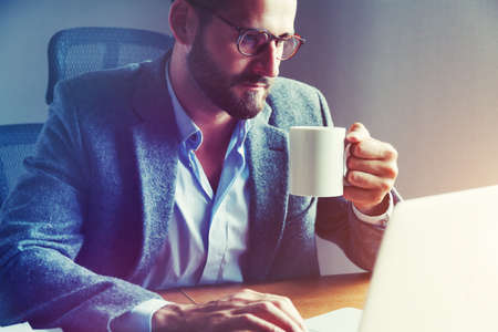 Handsome businessman drinking cup of morning coffee at table with laptop